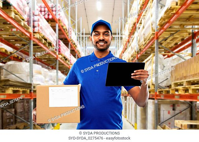 delivery man with tablet pc and box at warehouse