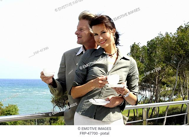 Couple at the sea is drinking coffee