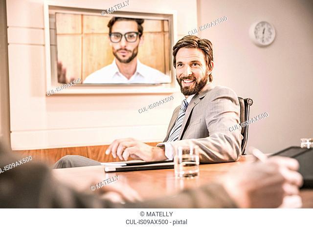 Business people in boardroom having video call meeting