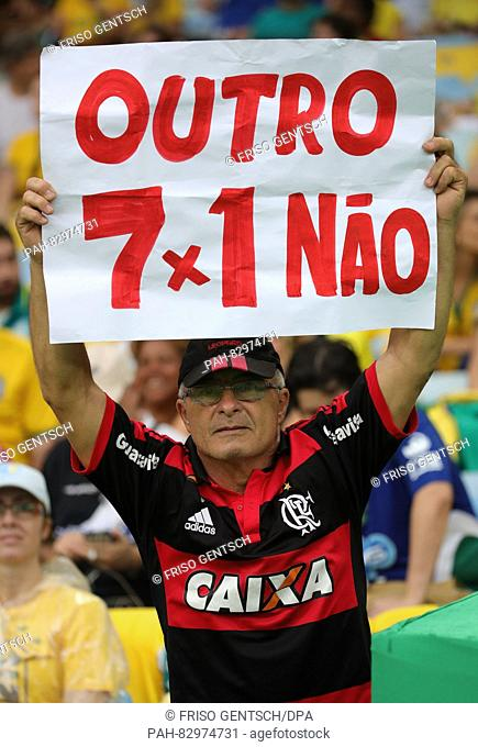 A supporter of Brazil holds up a poster reading 'Not another 7-1', in reference to the 2014 World Cup semifinal defeat of Brazil to Germany