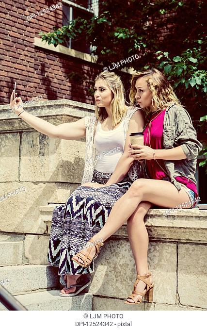 Two female university students sitting together on the campus taking a self-portrait with their smart phone and making silly pouty lips; Edmonton, Alberta
