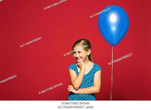 Girl with hand under chin, balloon suspended behind her