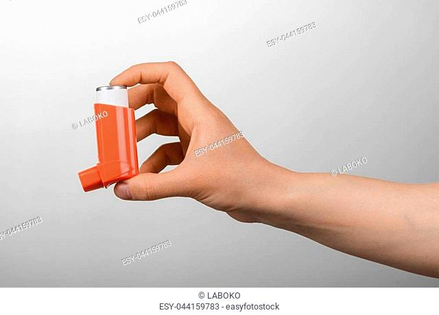 Small portable inhaler in female hand on gray background