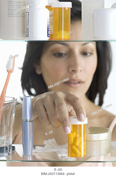 Young woman taking pills out of medicine cabinet