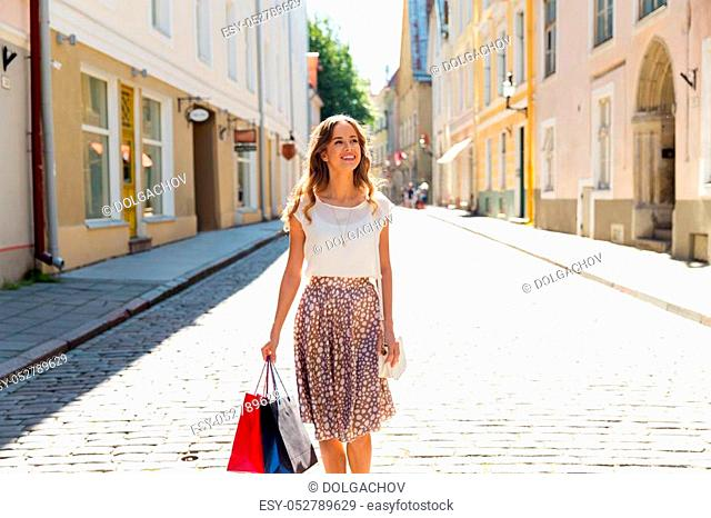 sale, consumerism and people concept - happy young woman with shopping bags on city street