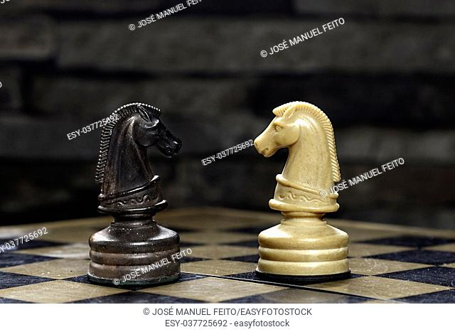 Chess horses faced with chessboard with stone