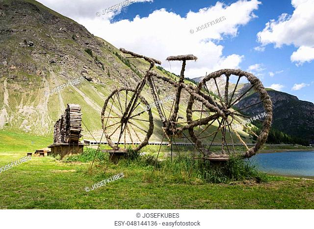 Bicycle straw sculpture in front of Lake Livigno, Italy