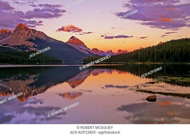 Evening alpenglow on mountain ranges surrounding Maligne Lake. Jasper National Park, Alberta, Canada