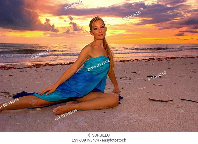 A vibrant tropical sunset over the ocean with an attractive blonde haired woman stretched out on the beach looking directly at viewer