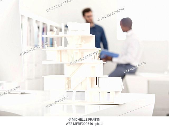 Architectural model on desk in an office with two talking people in the background