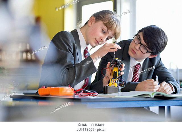 High school students assembling robot in science class