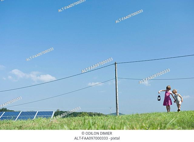 Children walking in field near solar panels and power lines, carrying old-fashioned lantern