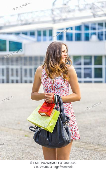 Young woman shopper happy called looking back distracted