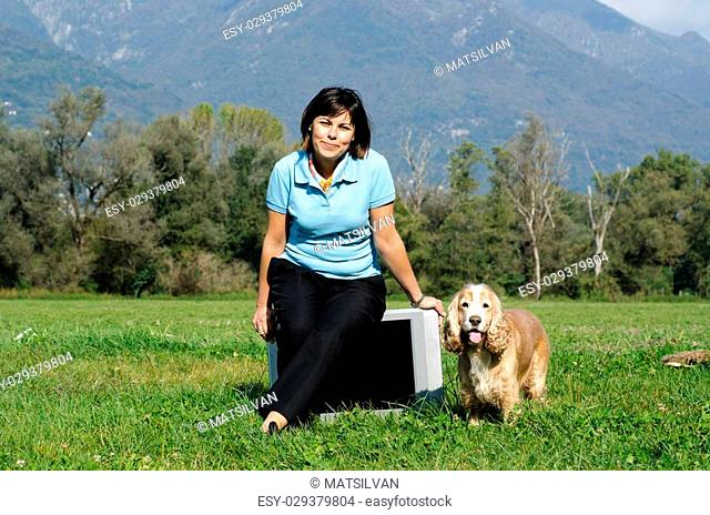 Elegant woman sitting on the television and she have a dog