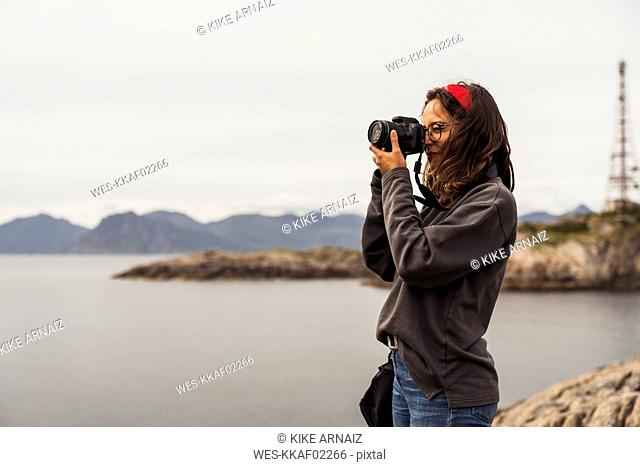 Young woman taking pictures of a lake in Vesteralen Island, Lapland, Norway
