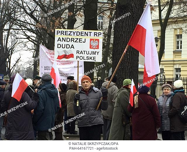 A small group of pro-government demonstrators carry a sign that reads 'President Andrzej Duda, let us save Poland' during a rally held in front of the...
