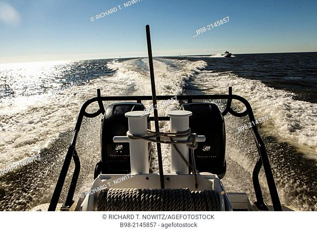 The wake from a police speed boat with an outboard motors in the Gulf of Mexico