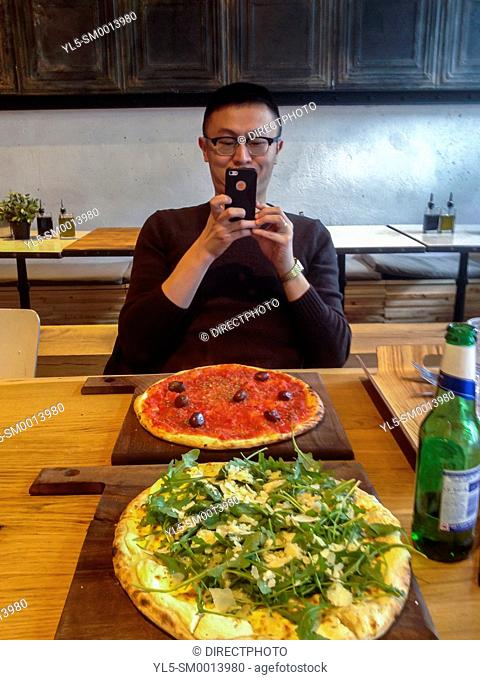 Paris, France. Chinese Man Taking Photos with Iphone of Pizza in italian Restaurant in Bibliotheque District