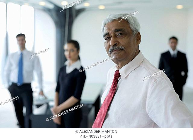 India, Senior business man standing in front of colleagues