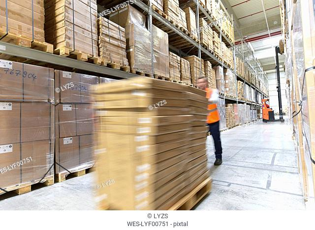 Man in factory hall transporting goods