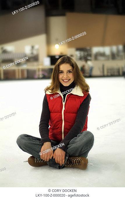 Portrait of ice skater sitting on ice