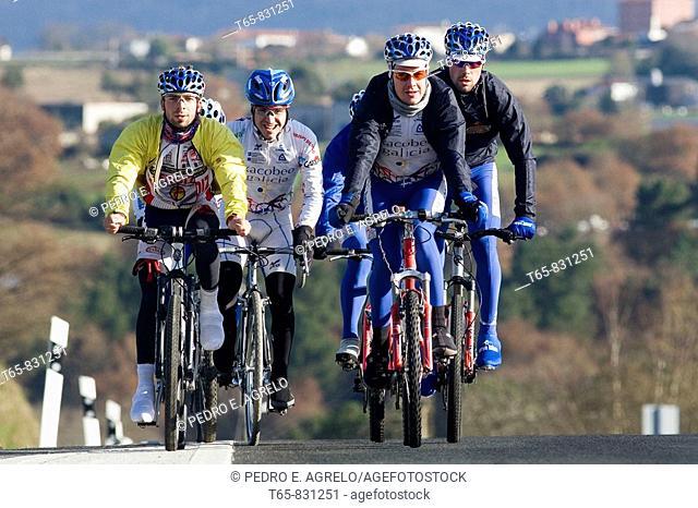 the cycling peloton Xacobeo Galician group cycling, Jacobea route, going through the road to Santiago de Compostela, in the background the town of Arzua