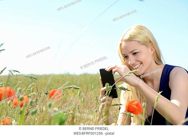 Young woman photographing poppies with smartphone