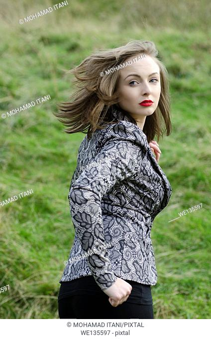 Scared young woman running away looking over shoulder