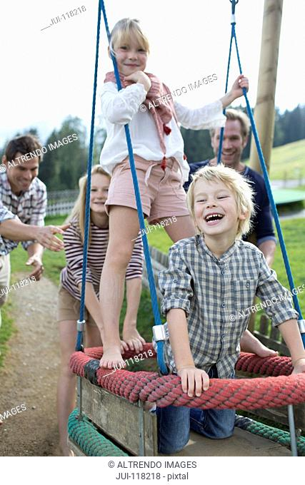 Father Pushing Children On Swing In Adventure Playground