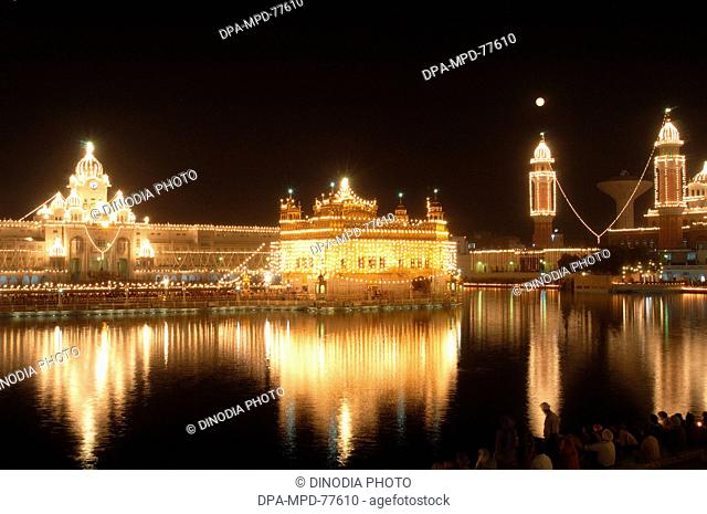 An illuminated Golden Temple ; also known as Harimandir Granth Sahib ; sacred place of worship of Sikhs at Amritsar ; Punjab ; India on the occasion of birth...