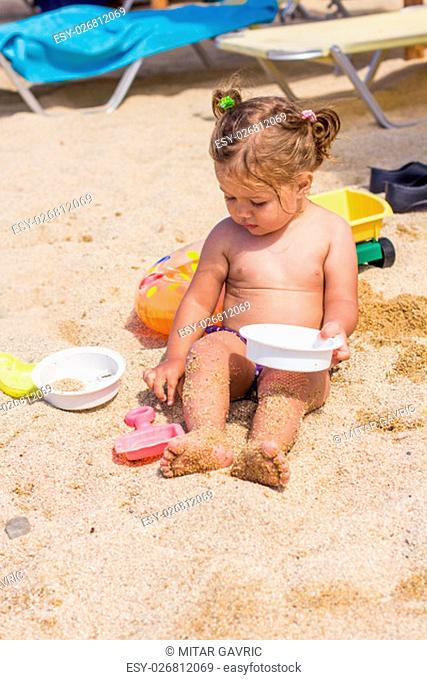 Adorable Little Girl Playing with toys at sandy beach. Summer vacation