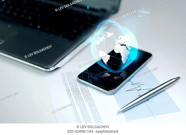 business, technology and communication concept - close up of smartphone with earth globe hologram, laptop computer and chart with pen on office table
