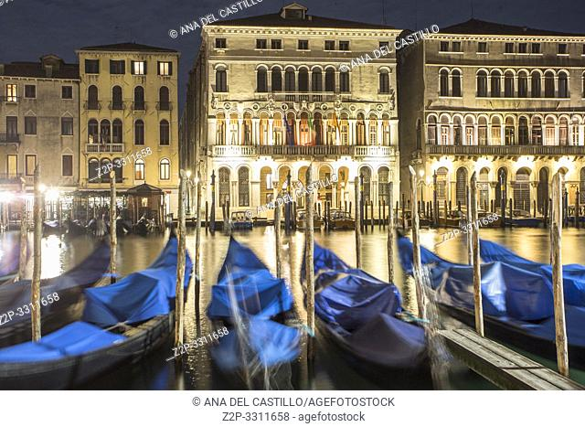 Moored gondolas sway with the the movement of the water along the Grand Canal in Venice, Italy