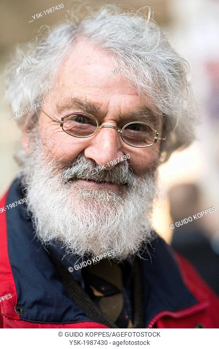 Maastricht, Netherlands. Elder man with grey facial hair and glasses, being a visitor at a Dutch design fare