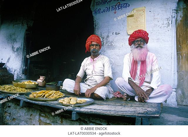 Local men wearing red traditional turban. Beard dyed pink from holy paint throwing. Food shop. Trays. Teapot