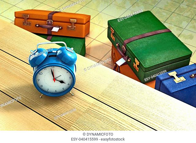 Alarm clock on a table with suitcases as background