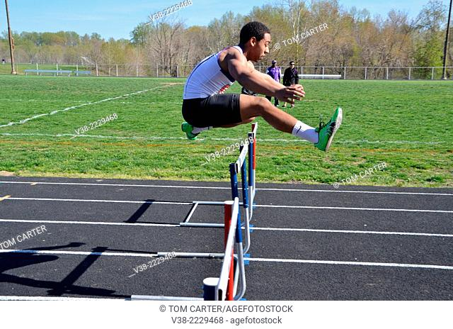 teen jumping hurdles in a track and meet event