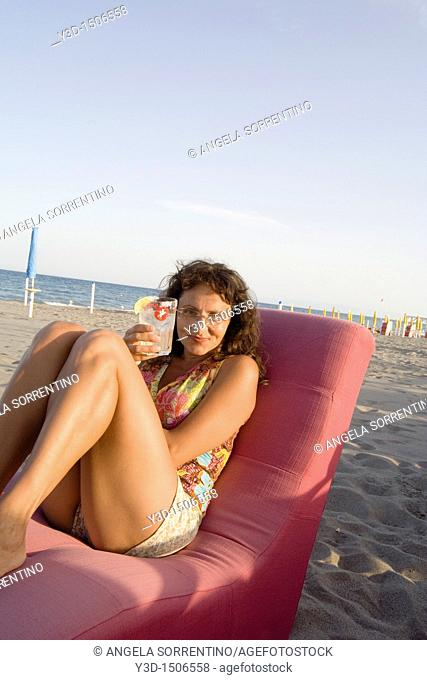 Woman smiling and drinking on a beach, Basilicata, Italy