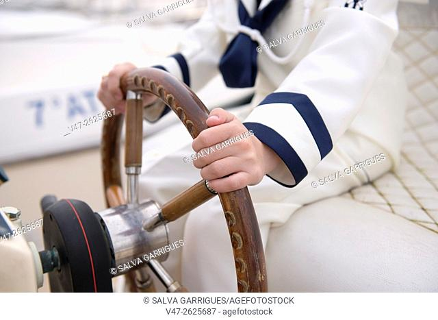 Detail of the hands of a child taking the helm of a ship, sailor dress on the day of his first communion Valencia, Spain, Europe