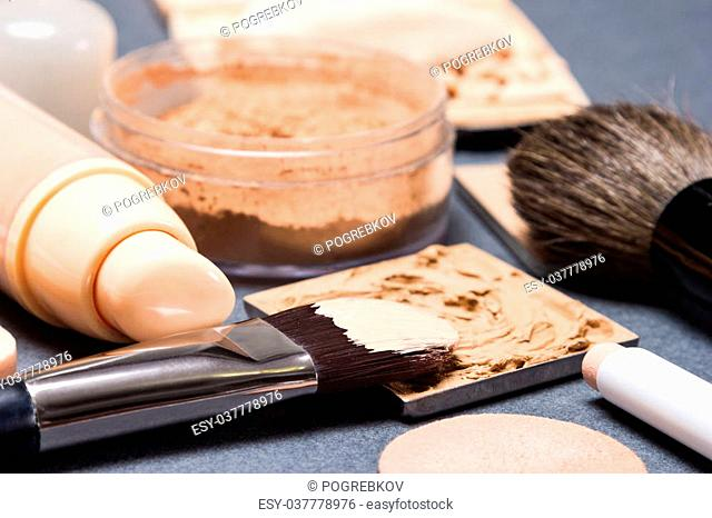 Makeup products and accessories to even out skin tone and complexion on gray textured surface. Side view, very shallow depth of field