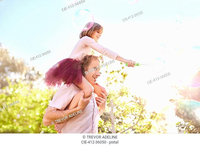 Father carrying daughter with bubble wand on shoulders in sunny summer park
