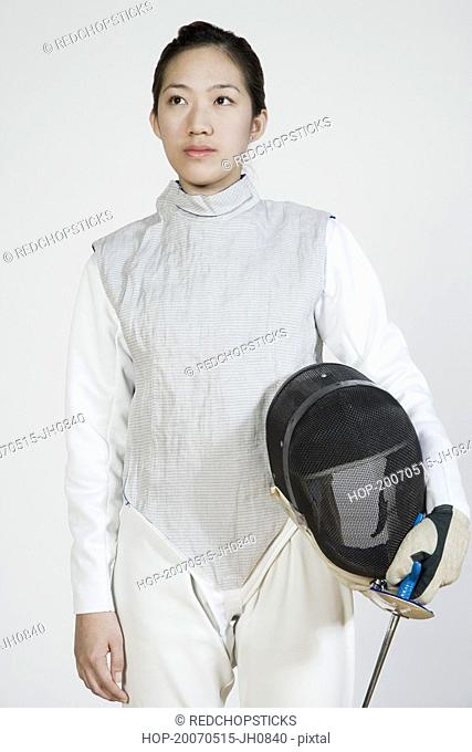 Close-up of a female fencer holding a fencing foil and a fencing mask