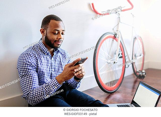 Man sitting on wooden floor with laptop and cell phone and bicycle next to him