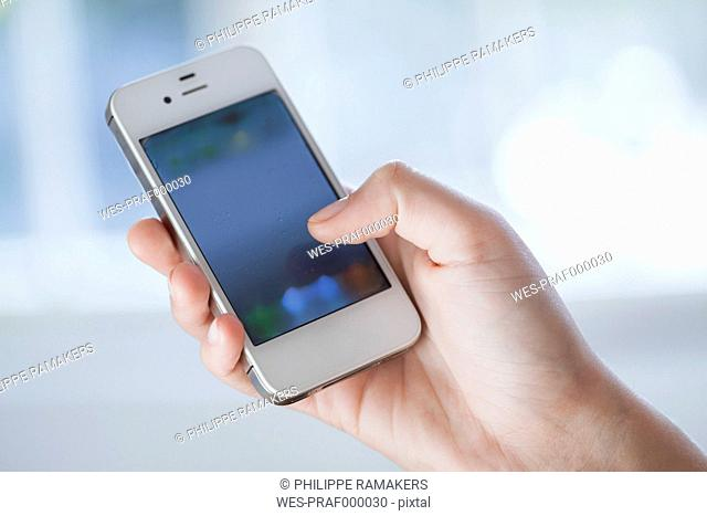 Young woman using smart phone, close up