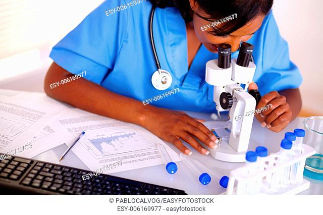 Pretty nurse working at laboratory in blue uniform with a microscope