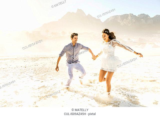 Couple running and splashing in sunlit sea, Cape Town, South Africa