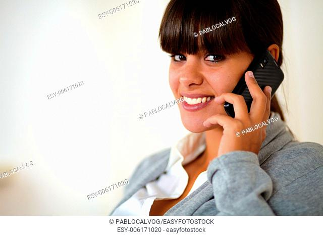 Portrait of a young female smiling and looking at you speaking on cellphone