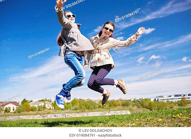 people, children, friends and friendship concept - happy little girls jumping high outdoors