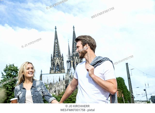 Germany, Cologne, happy young walking hand in hand