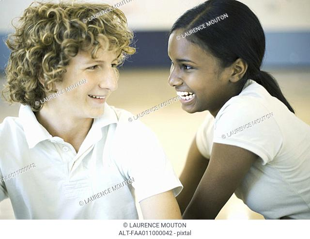 Teen couple smiling at each other
